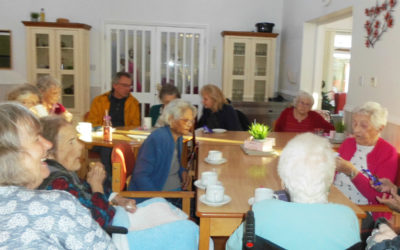 Woodstock Residential Care Home residents and family members sitting together at their Home meeting