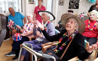 Seated residents enjoying a sing along, wearing hats and garlands