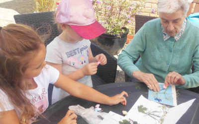 Resident with two pre-school children doing crafts in the garden