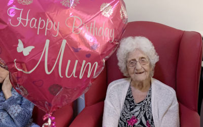 Lady resident with a heart shaped birthday balloon