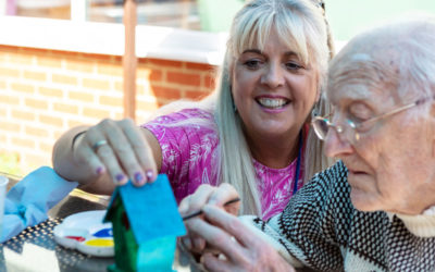 Christine Foster, Recreation & Well-Being Manager, with a resident painting a birdhouse together