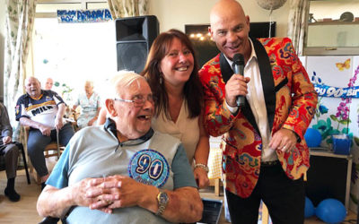 Male resident at Silverpoint Court on his birthday with a singer in the lounge