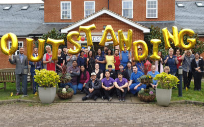 Staff outside Princess Christian Care Home holding balloons which spell out Outstanding