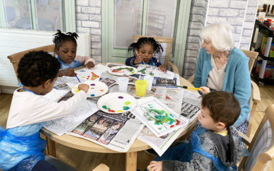 A lady resident sitting with a group of nursery children who are painting pictures